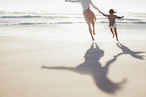 Mother and daughter holding hands and running on sunny beach - gettyimageskorea