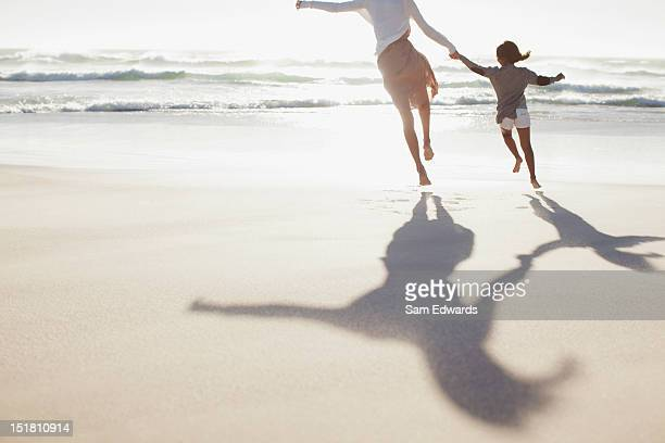 mother and daughter holding hands and running on sunny beach - shadow stock pictures, royalty-free photos & images