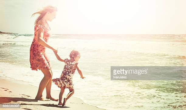 Mother and daughter holding hands at waves