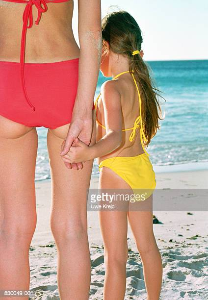 Mother and daughter (4-6) holding hands, facing sea, rear view
