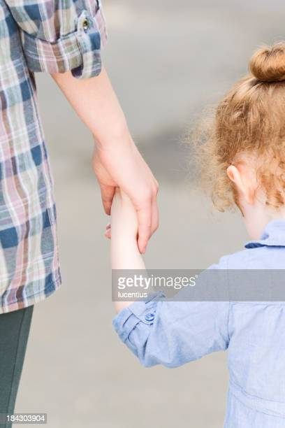Mother and daughter holding hands in a loving bond