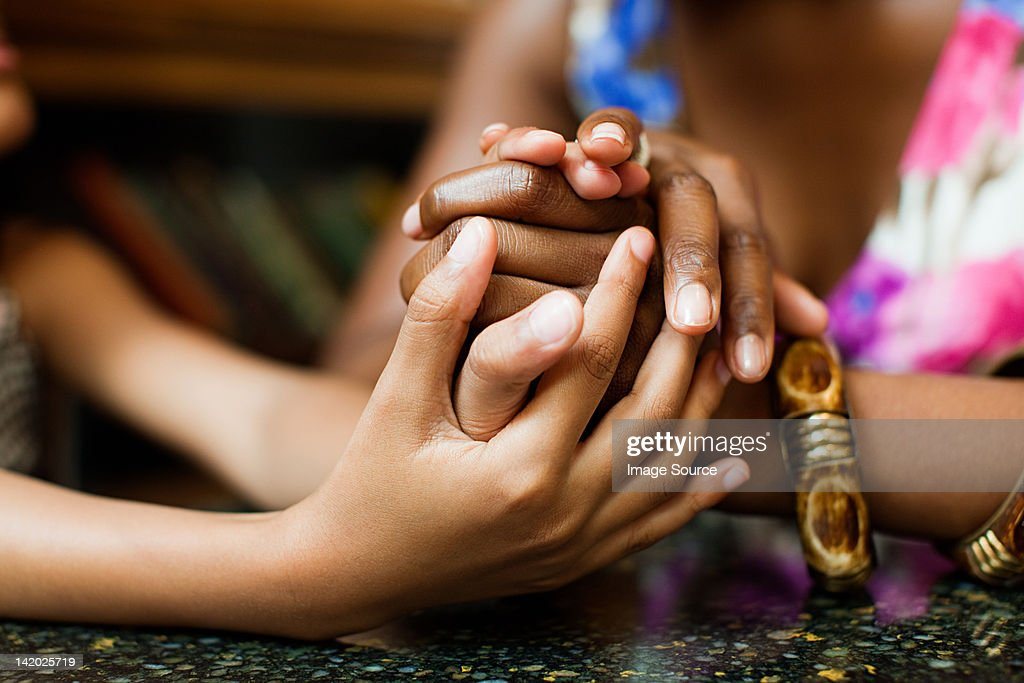 Mother and daughter holding hands in cafe : Stock Photo