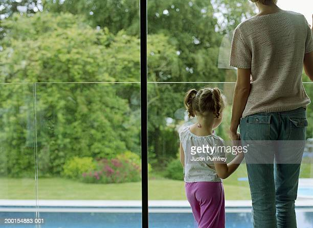 Mother and daughter (3-5) holding hands, looking out window, rear view