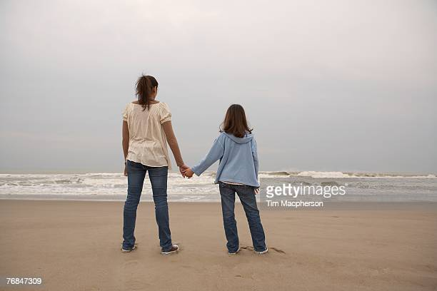 Mother and daughter (9-11) holding hands on beach, rear view