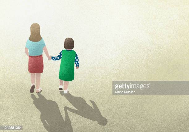 Mother and daughter holding hands on yellow background