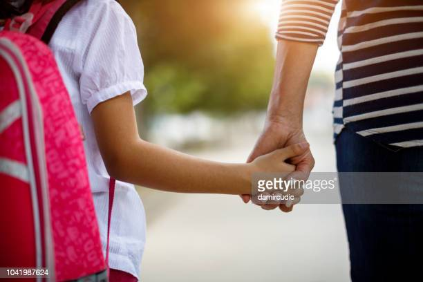 mother and daughter holding hands - genitori foto e immagini stock