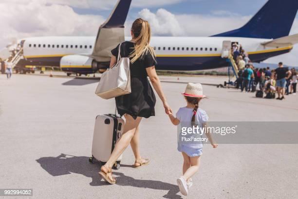 mutter und tochter, die hand in hand beim einsteigen in ein flugzeug - einsteigen stock-fotos und bilder