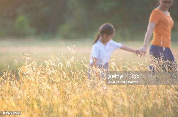 Mother And Daughter Holding Hands While Walking On Field During Sunny Day