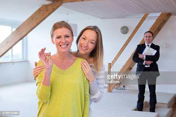 Mãe e filha segurando as chaves de sua nova casa