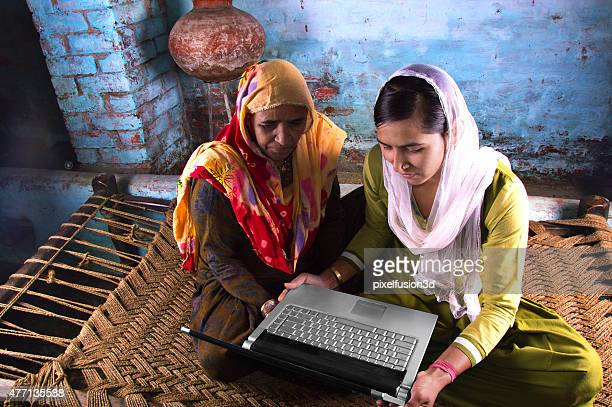 Mother and Daughter Holding Laptop at Home