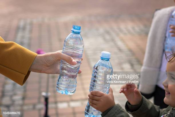 Mother And Daughter Holding Water Bottles In City