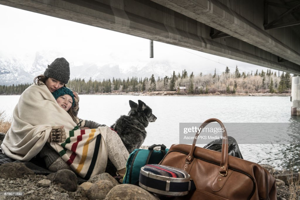 Mother and daughter huddle at roadside, with belongings : Stock Photo