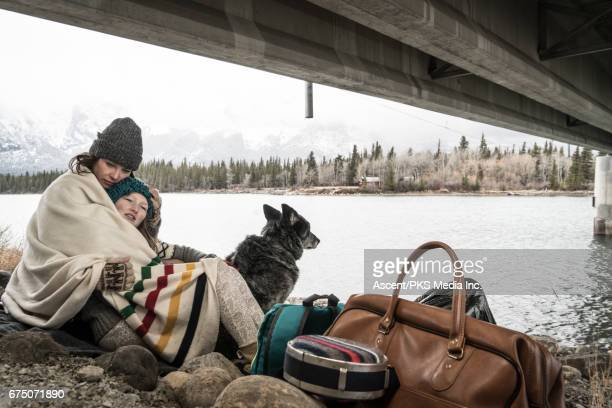 Mother and daughter huddle at roadside, with belongings