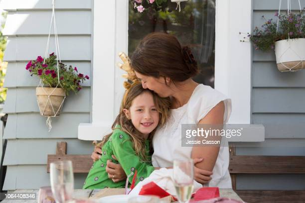 A mother and daughter hug at the Christmas lunch table
