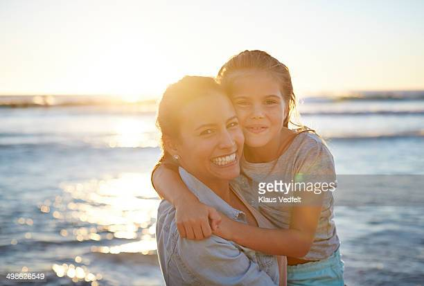 Mother and daughter hugging at beach