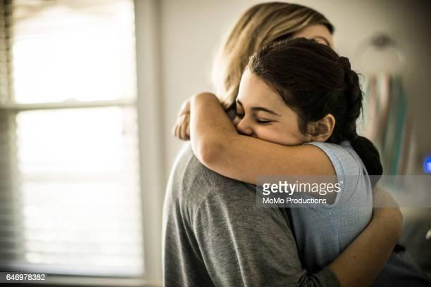 Mother and daughter (7yrs) hugging, closeup