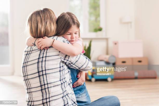 Mother and daughter hugging in empty apartment