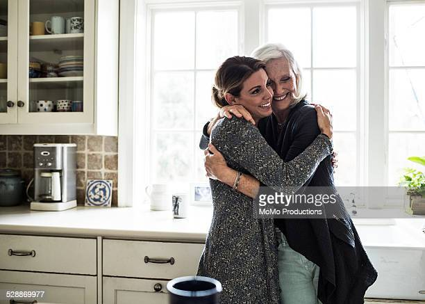 mother and daughter hugging in kitchen
