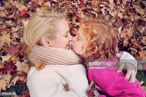 "mother and daughter hugging lying down on fallen leaves. - ""martine doucet"" or martinedoucet stockfoto's en -beelden"