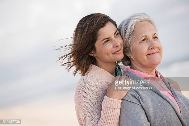Mother and daughter hugging on beach