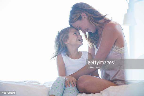 mother and daughter hugging on bed - little girls undies stock pictures, royalty-free photos & images
