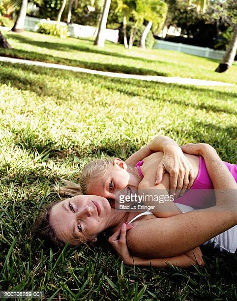mother and daughter (9-11) hugging on lawn, portrait, elevated view - blasius erlinger stock pictures, royalty-free photos & images