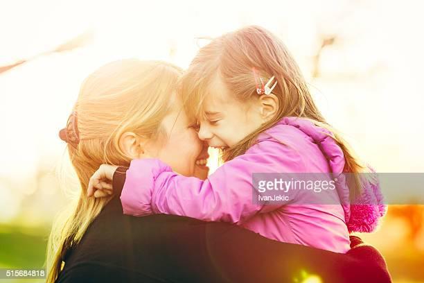 Mother and daughter hugging outdoors closeup