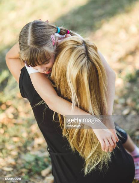 mother and daughter hugging outdoors - ivanjekic stock pictures, royalty-free photos & images