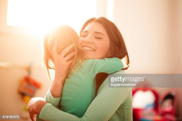 mother and daughter hugging - omarmd stockfoto's en -beelden
