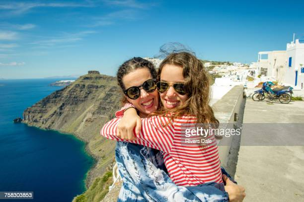 mother and daughter hugging, sea in background, oa, santorini, kikladhes, greece - パイロットサングラス ストックフォトと画像