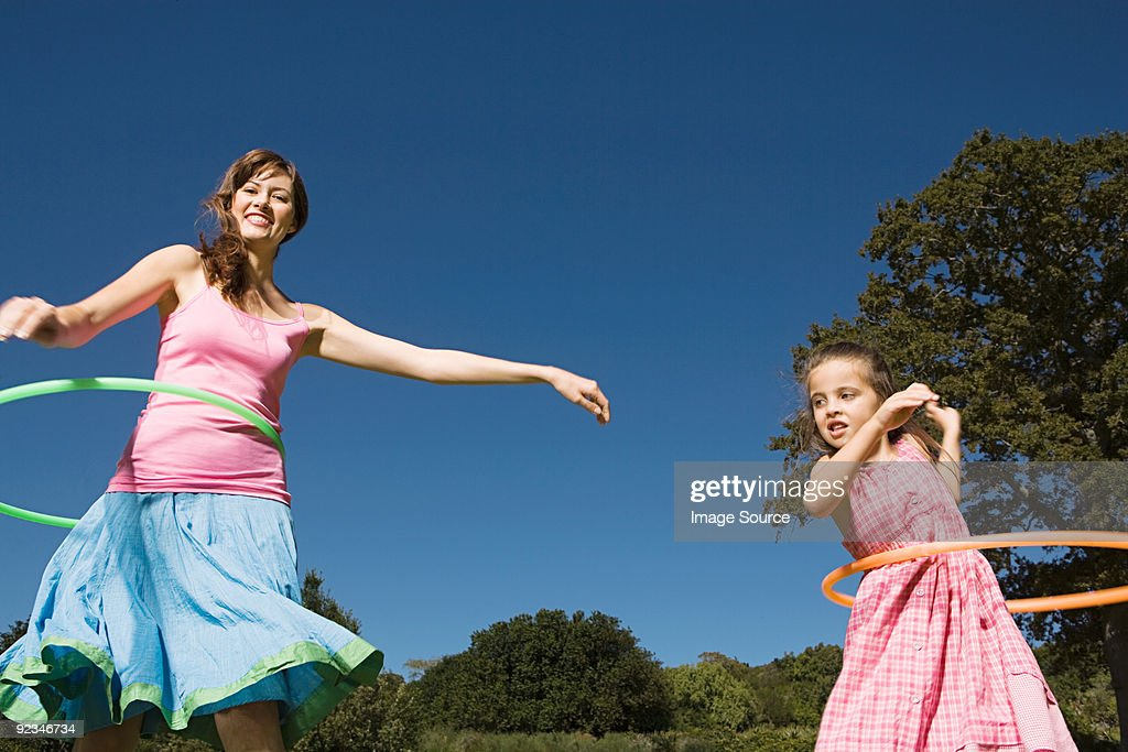 Mother and daughter hula hooping : Stock Photo