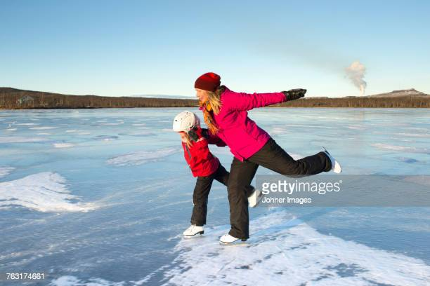 mother and daughter ice-skating on frozen lake - swedish lapland stock photos and pictures