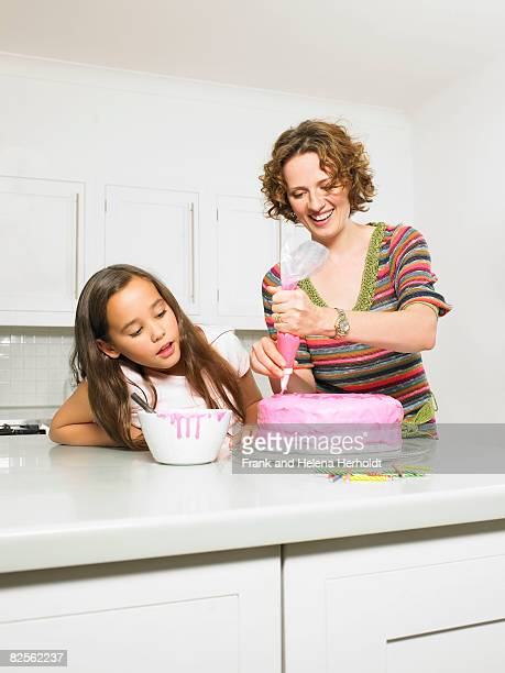 mother and daughter icing cake - decorating a cake stock pictures, royalty-free photos & images