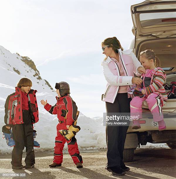 Mother and daughter (3-5) in back of vehicle watching boys (6-10)