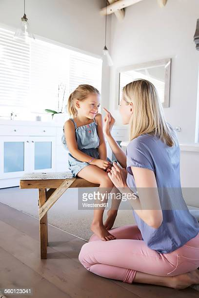 Mother and daughter in bathroom applying face cream