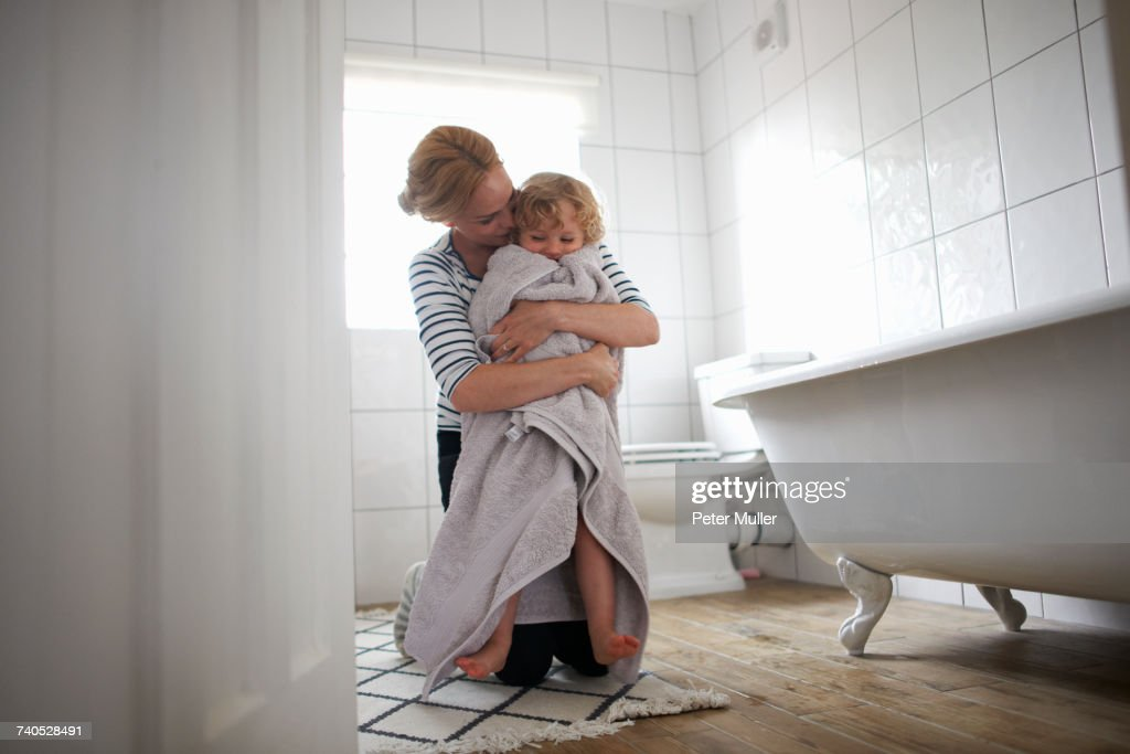 Mother and daughter in bathroom, mother wrapping daughter in bath towel, hugging her : Stock Photo