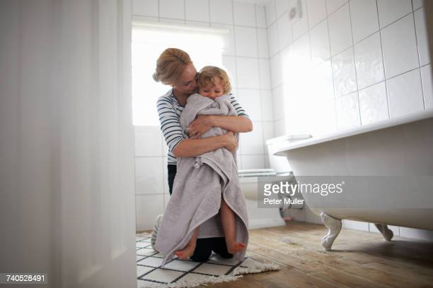 Mother and daughter in bathroom, mother wrapping daughter in bath towel, hugging her