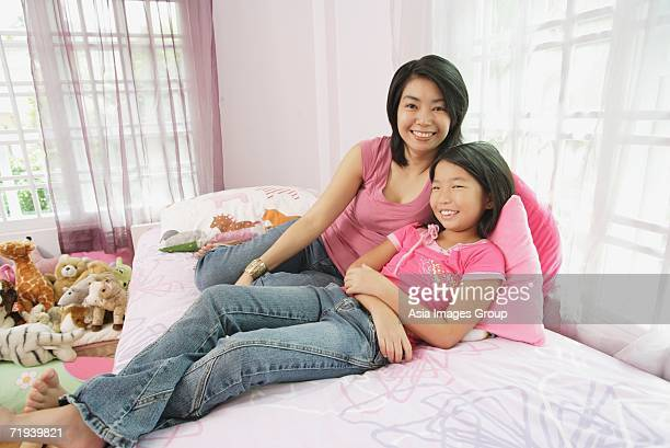 Mother and daughter in bedroom, side by side, looking at camera
