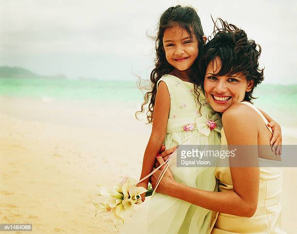 Mother and Daughter in Bridesmaids Dresses With Their Arms Around Each Other on a Windy Beach