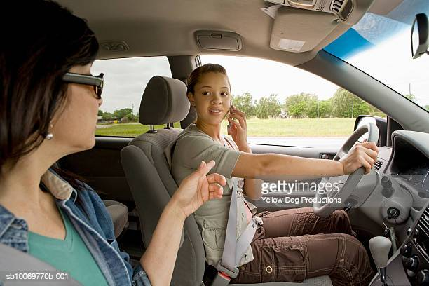 Mother and daughter (16-17) in car, teenage girl talking on mobile phone