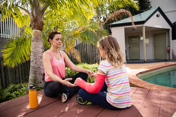 Mother and daughter in cast meditate at pool