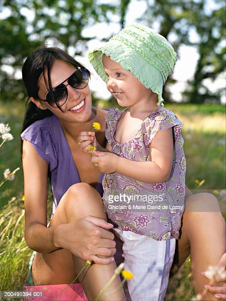 mother and daughter (18-21 months) in field, girl holding flower - saint ferme stock pictures, royalty-free photos & images