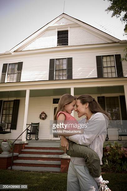 Mother and daughter (6-8) in front of house, smiling