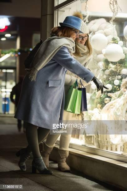 お店の窓の前の母と娘、クリスマスタイム