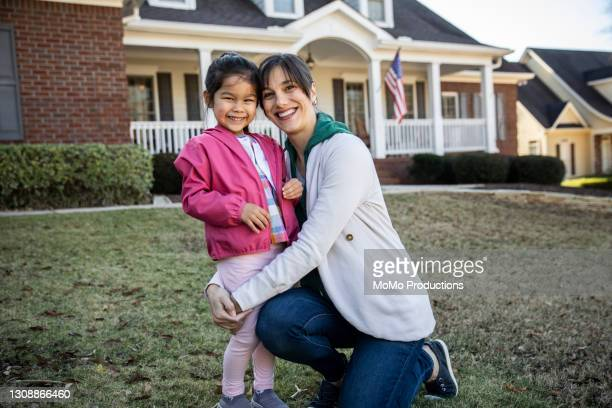 mother and daughter in front of suburban home - mortgage stock pictures, royalty-free photos & images