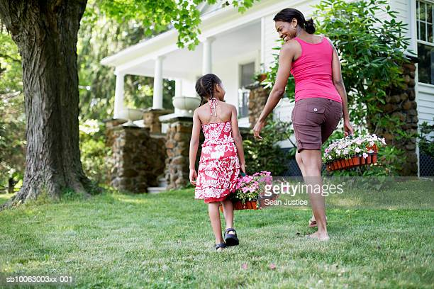 Mother and daughter (8-9 years) in garden outside house, carrying flowers, rear view