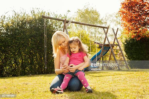 Mother and daughter in garden, swings in background