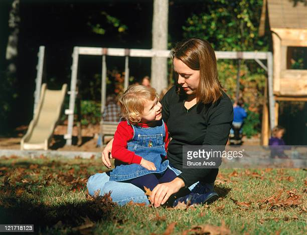 Mother and daughter in grass at playground