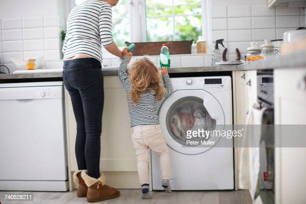 Mother and daughter in kitchen, daughter helping mum with washing up