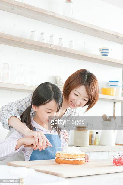 Mother and daughter in kitchen decorating cake, Hyogo Prefecture, Honshu, Japan